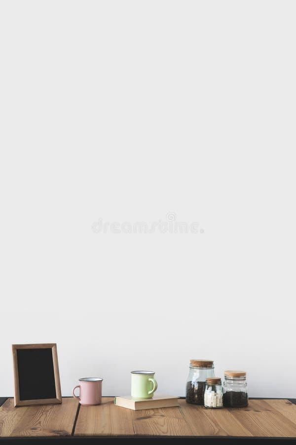 lavagna vuota nel telaio con le tazze ed il caffè sulla tavola di legno immagine stock libera da diritti