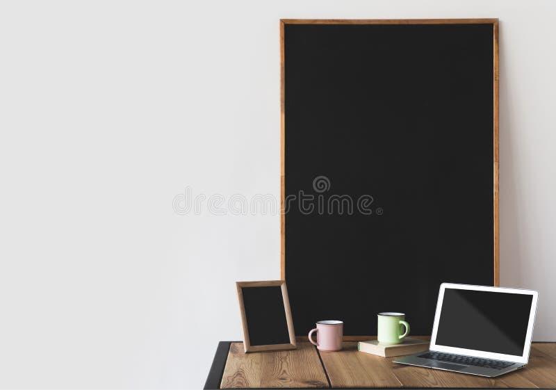 lavagne vuote nei telai con le tazze ed il computer portatile immagine stock libera da diritti