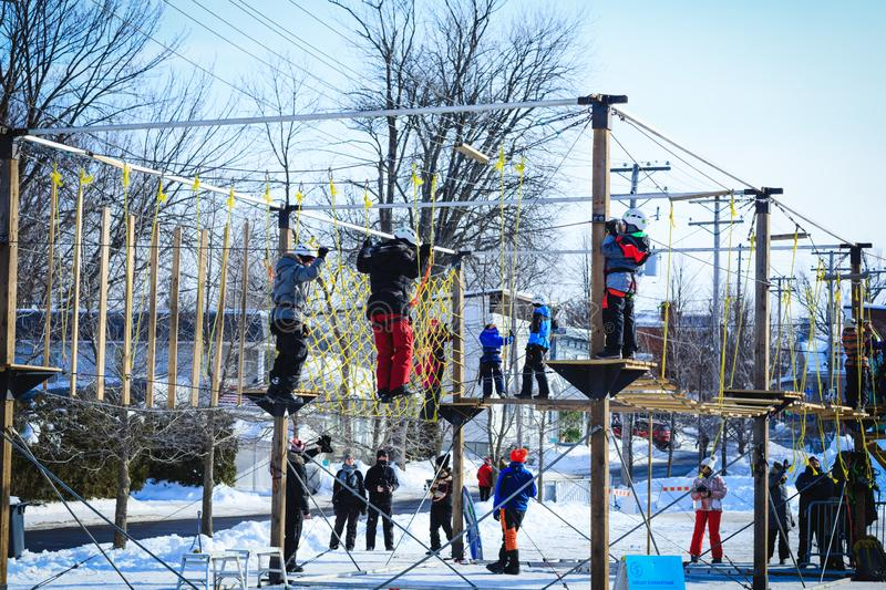 Laval, Canada - January, 2019. Kids climbing a rope playground during the winter vacation. Boys and girls having fun in an. Adventure park. Children and parents stock photography
