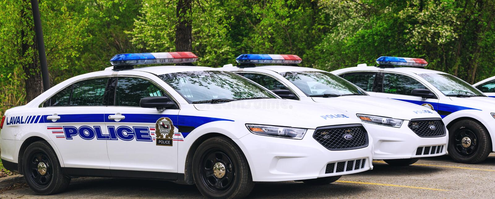 Laval, Canada: May 19, 2018. Police cars parked in the parking a. Rea of the public park. A lot of police cars stationed in line, before leaving to the mission royalty free stock image