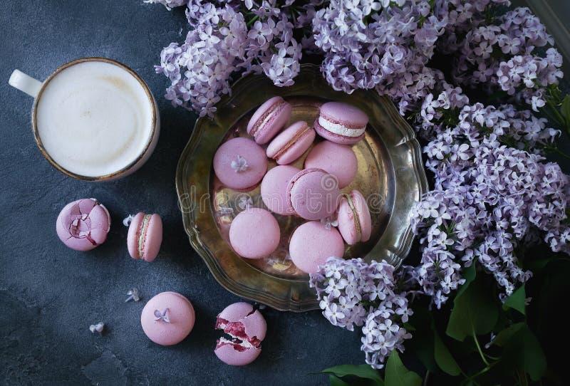 Lavander lub czarnych jagod macarons z waniliowym ganache na stole rocznika srebnego talerza i zmroku kamienia, dekorującym z lil obraz royalty free