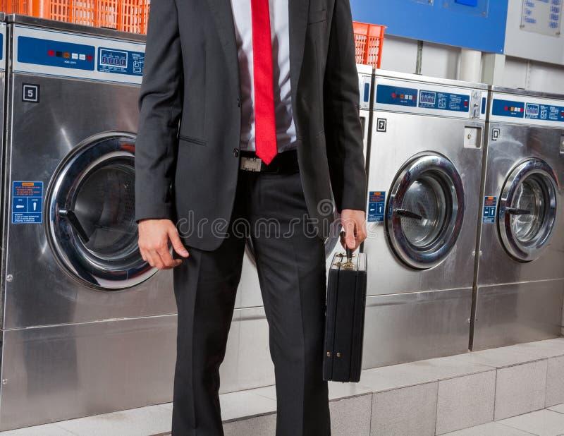 Lavanderia de Holding Suitcase In do homem de negócios foto de stock