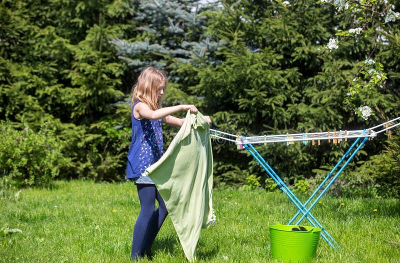Lavanderia de suspensão da menina no jardim fotos de stock