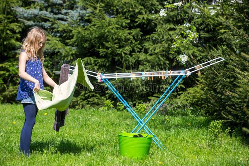 Lavanderia de suspensão da menina no jardim fotos de stock royalty free