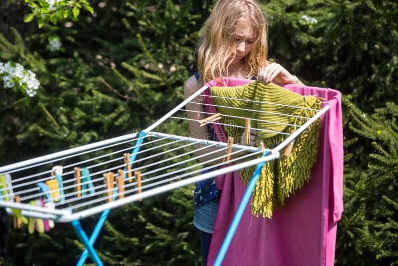 Lavanderia de suspensão da menina no jardim imagem de stock royalty free