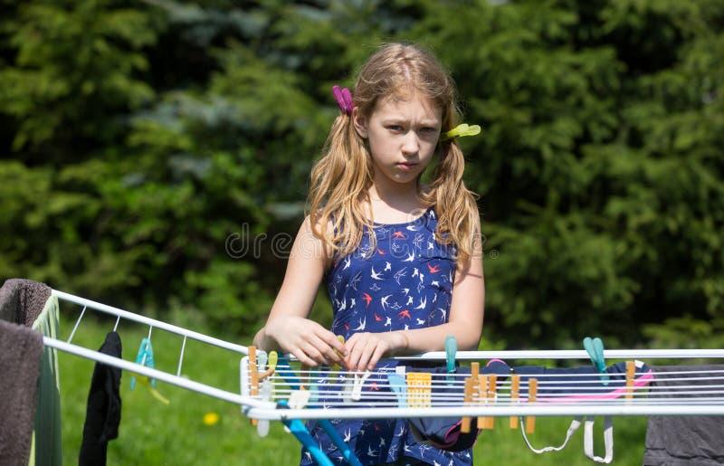 Lavanderia de suspensão da menina no jardim imagem de stock