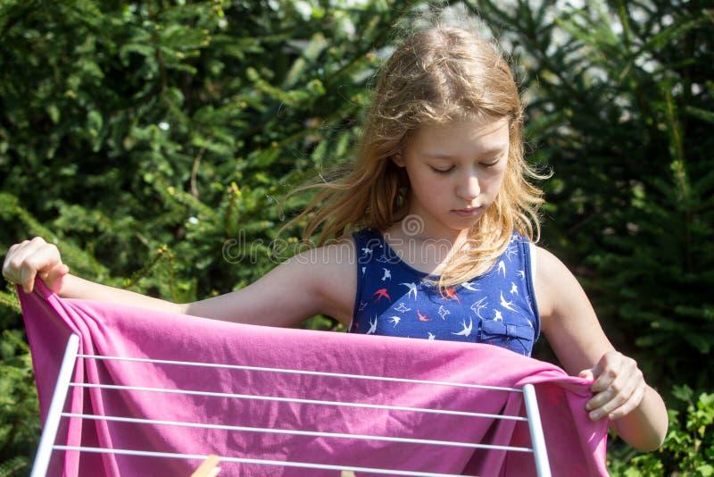 Lavanderia de suspensão da menina no jardim imagens de stock