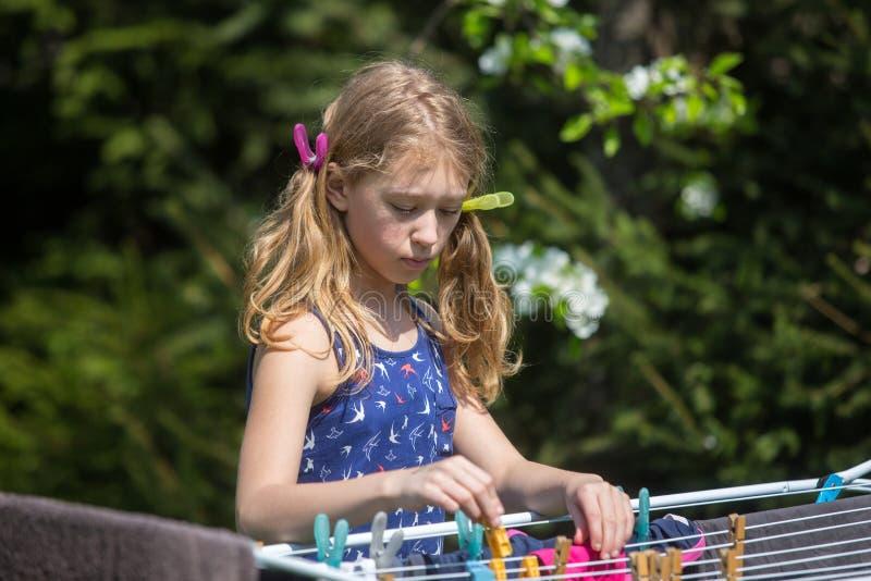 Lavanderia de suspensão da menina no jardim imagens de stock royalty free