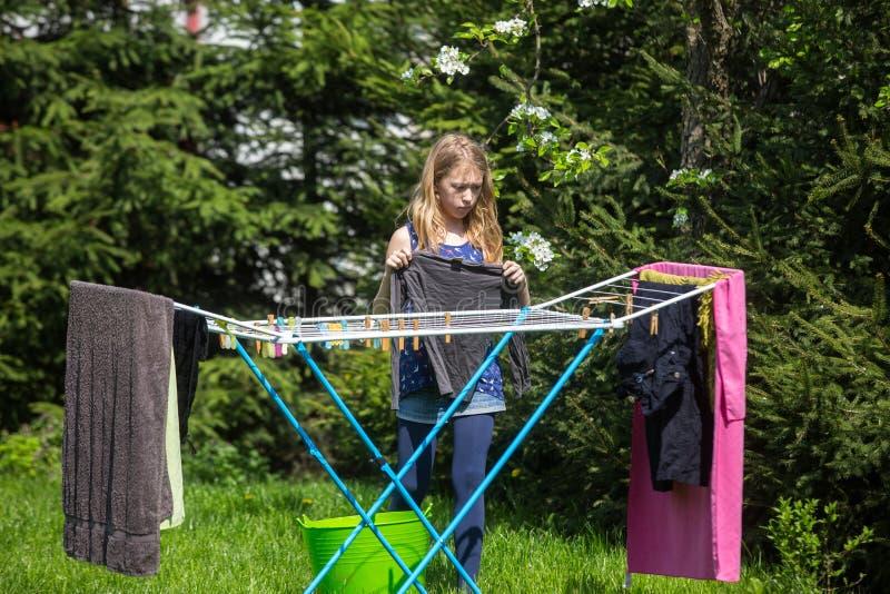 Lavanderia de suspensão da menina no jardim fotografia de stock
