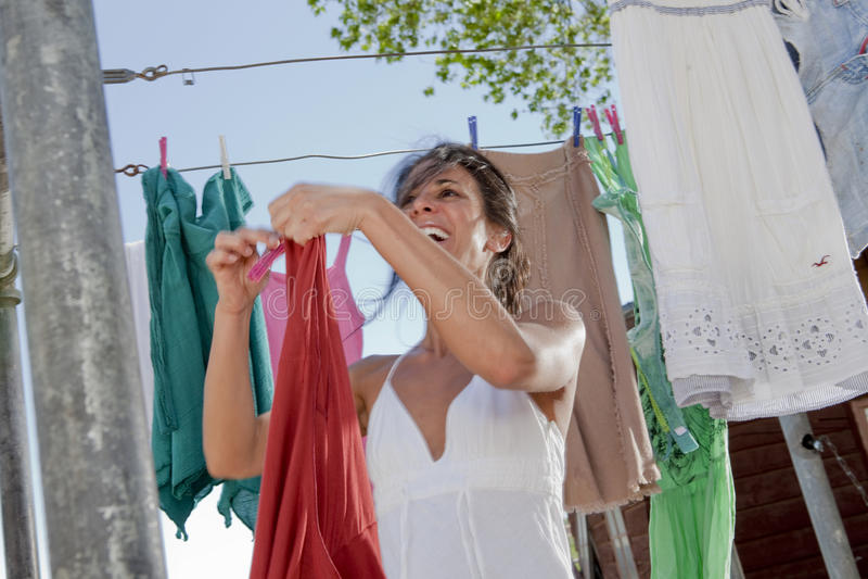 Lavanderia de suspensão da mulher no Clothesline fotografia de stock