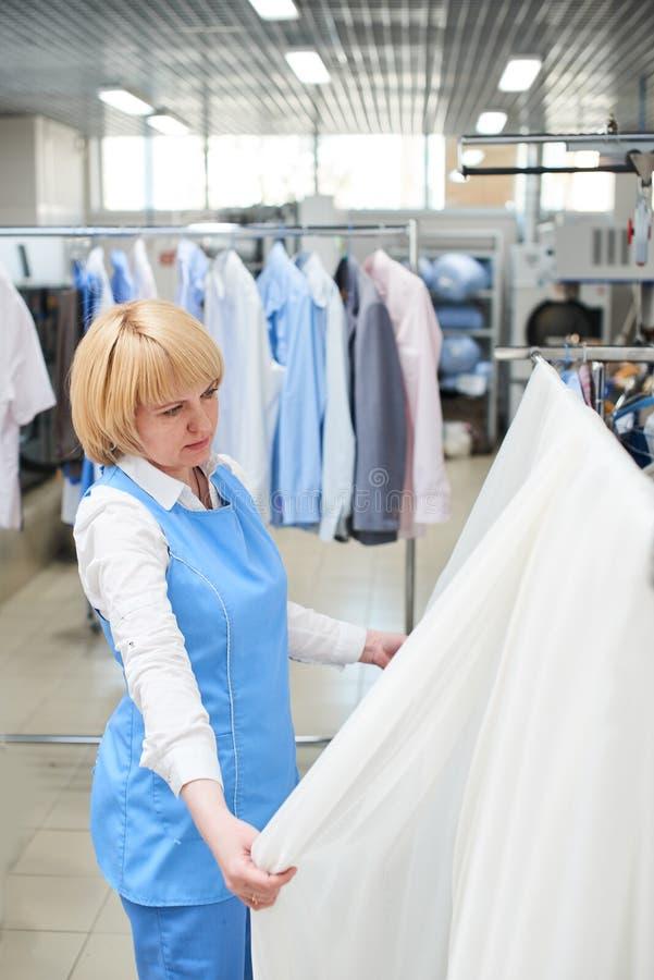 A lavanderia do trabalhador da menina olha e verifica do tule branco, completo imagem de stock