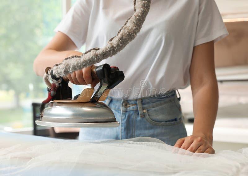 Lavanderia passando do trabalhador fêmea na lavagem a seco fotografia de stock
