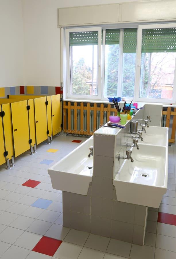 Lavandini per la pulizia dentro il bagno della scuola materna senza il bambino immagini stock libere da diritti