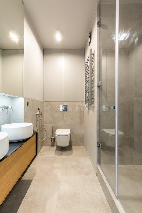 Lavandino bianco sul gabinetto di legno nel inte beige elegante del bagno fotografie stock