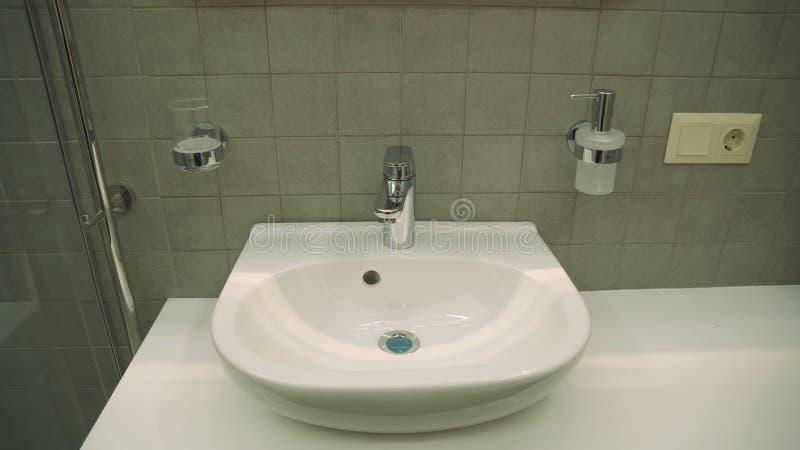 Lavandino ceramico con il rubinetto caldo e freddo nel bagno dell'albergo di lusso fotografie stock