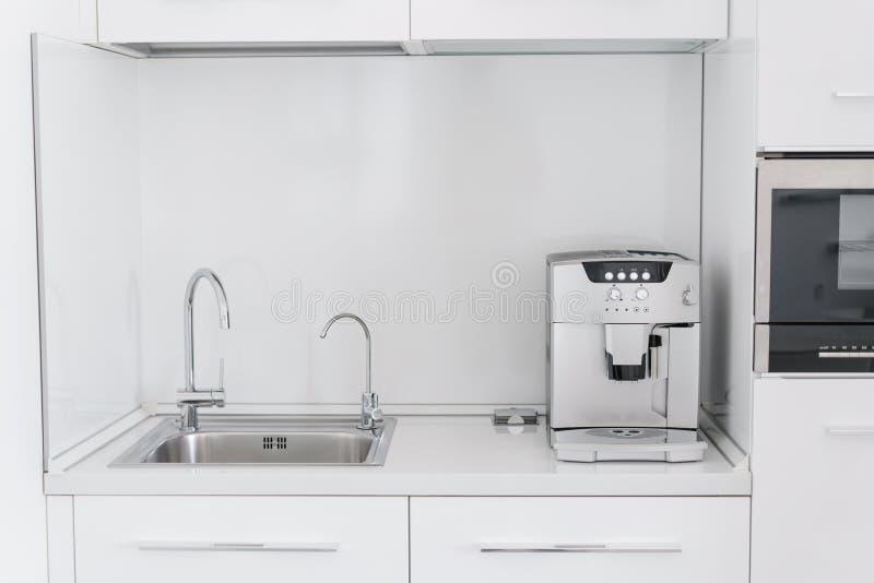 Lavandino del cromo del metallo con due rubinetti, la pianura ed acqua filtrata Frammento della cucina moderna con il contatore e fotografie stock
