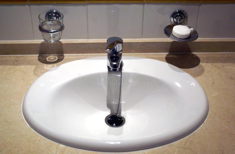 Lavandino del lavabo del bagno, rubinetto, tazza e compressa del sapone immagine stock