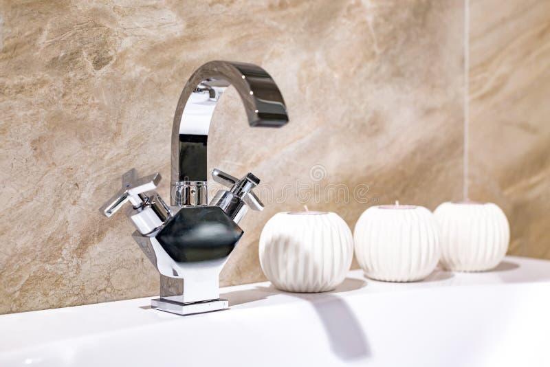 Lavandino del rubinetto di acqua con il rubinetto con le candele nel bagno costoso del sottotetto immagine stock