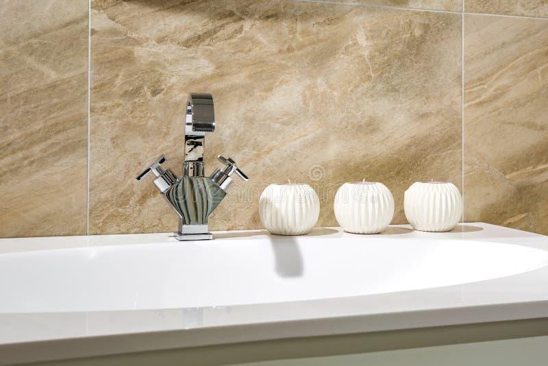 Lavandino del rubinetto di acqua con il rubinetto con le candele nel bagno costoso del sottotetto fotografie stock