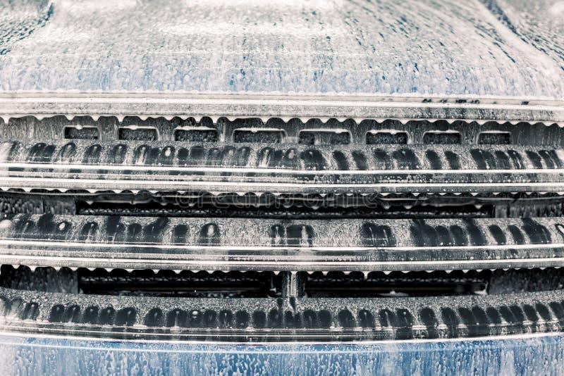 Lavando um carro, oficina de detalhes Feche a foto da grelha do radiador do carro de sabão durante a lavagem do carro com limpeza imagem de stock royalty free