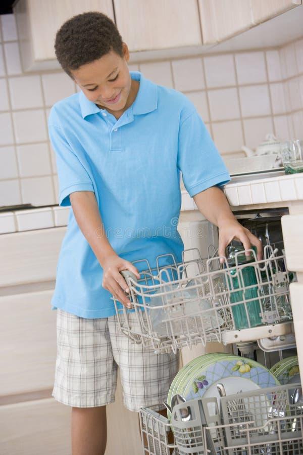 Lavaplatos joven del cargamento del muchacho imagen de archivo libre de regalías