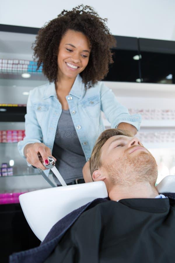 Lavar el pelo del cliente fotografía de archivo