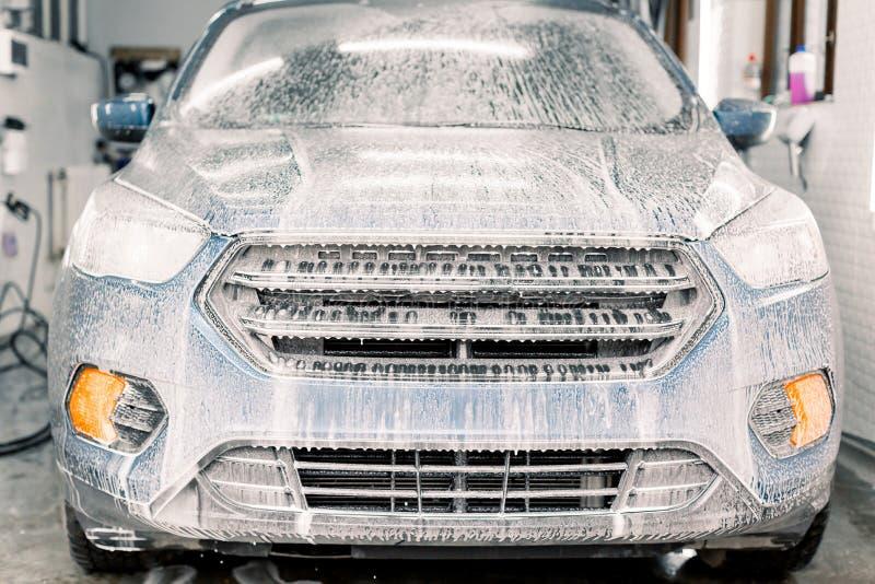 Lavar um carro no serviço de lavagem automática Carro azul de soja Lavagem do veículo cruzado com espuma de limpeza ativa, vista  imagem de stock royalty free
