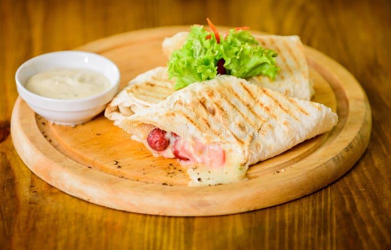 Lavash burrito faszerował mięsną kiełbasę i serowy kumberland słuzyć sałatki Mięso zawijający z lavash burrito Restauracyjny posi fotografia royalty free