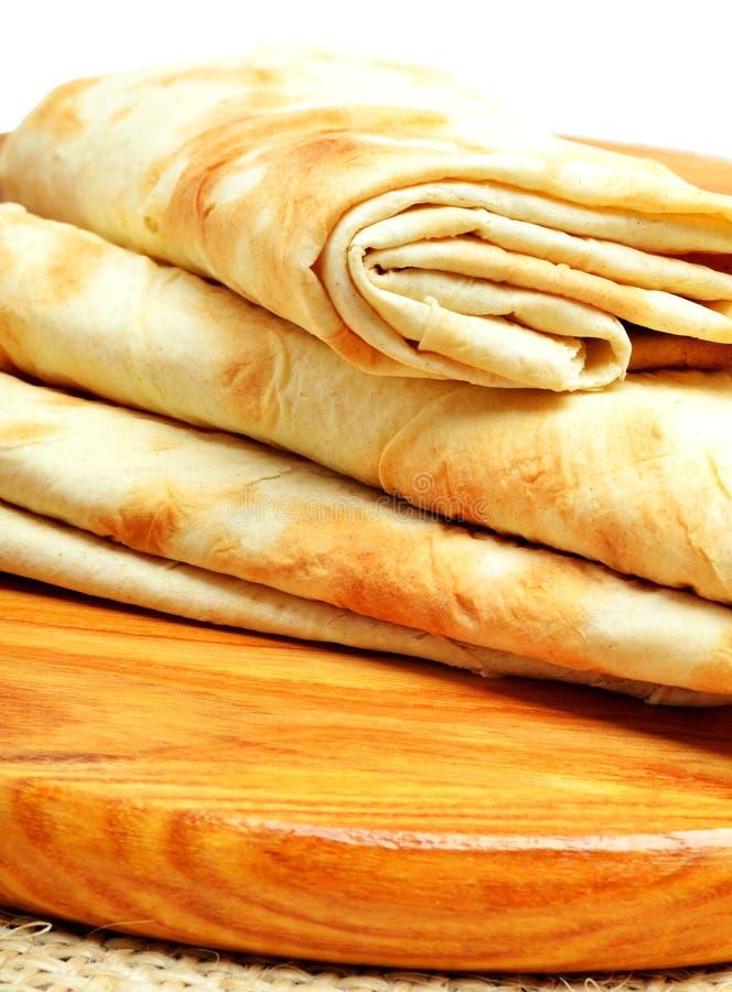 Lavash, pane dell'involucro della tortiglia sul tagliere su bianco immagini stock libere da diritti