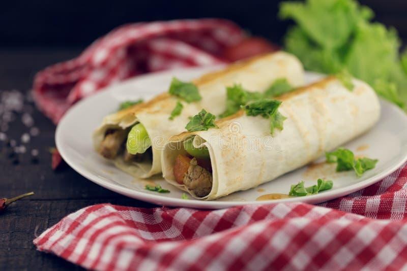 Lavash rola com a carne, os vegetais e o queijo servidos com verde foto de stock