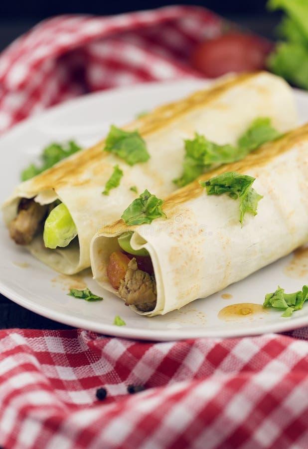 Lavash rola com a carne, os vegetais e o queijo servidos com verde imagem de stock