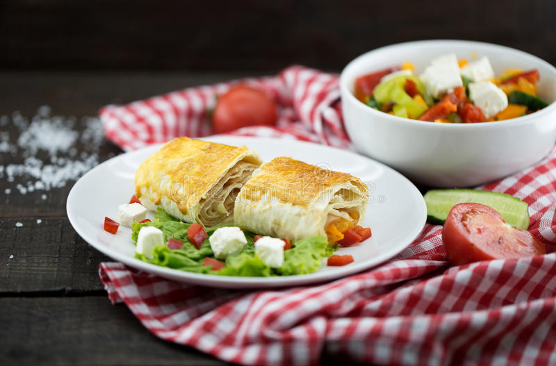 Lavash rolls with meet, vegetables and cheese served with green royalty free stock image