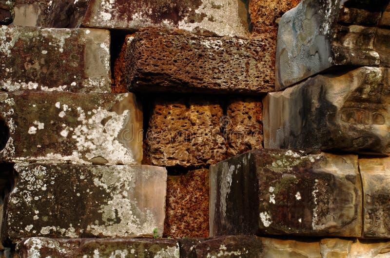 Lavastenar som omges av sandstenar i den Angkor templet arkivbilder