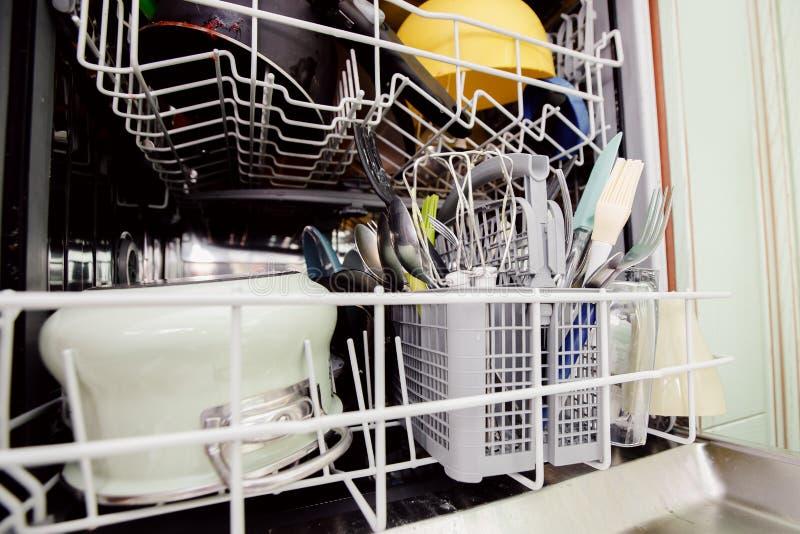 Lavastoviglie aperta con i piatti sporchi messi per lavare Risparmio dell'acqua di concetto immagine stock