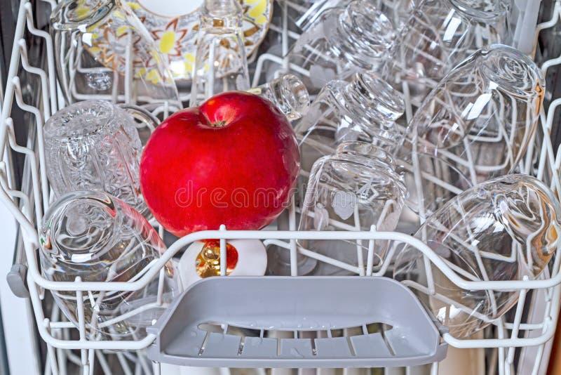 Lavastoviglie con i piatti e la mela puliti immagini stock libere da diritti