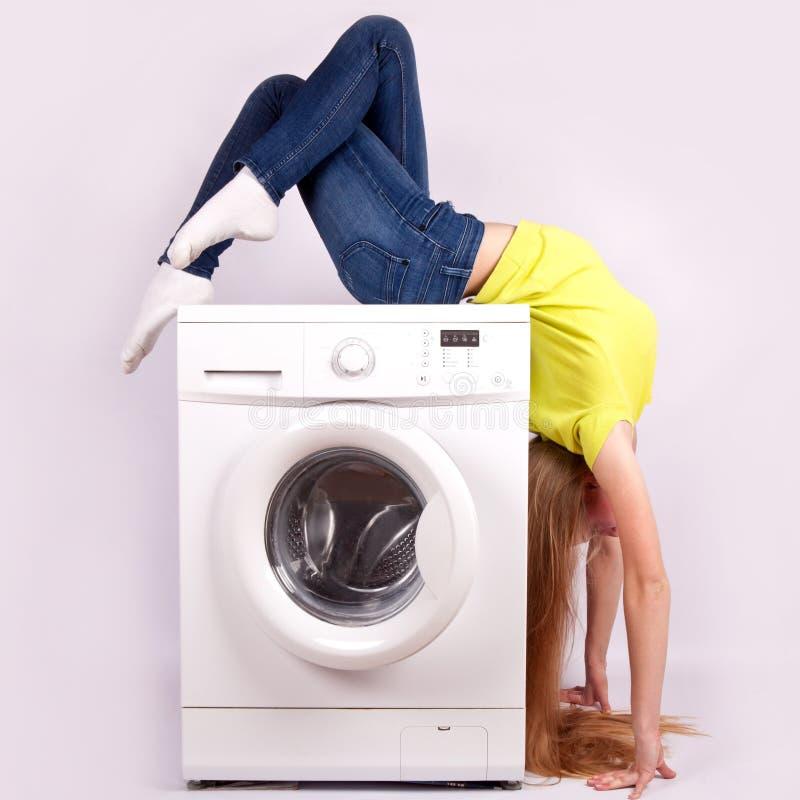 Lavatrice e bella donna isolate su fondo bianco apparecchi fotografia stock libera da diritti