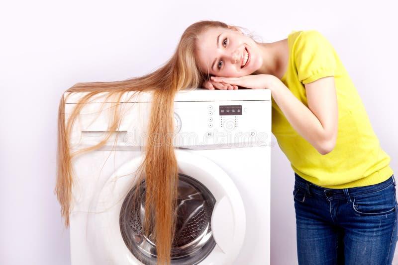 Lavatrice e bella ragazza bianca su fondo bianco fotografia stock
