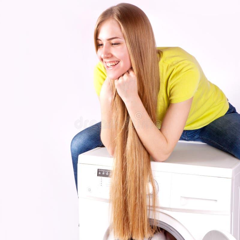 Lavatrice e giovane donna su fondo bianco fotografia stock