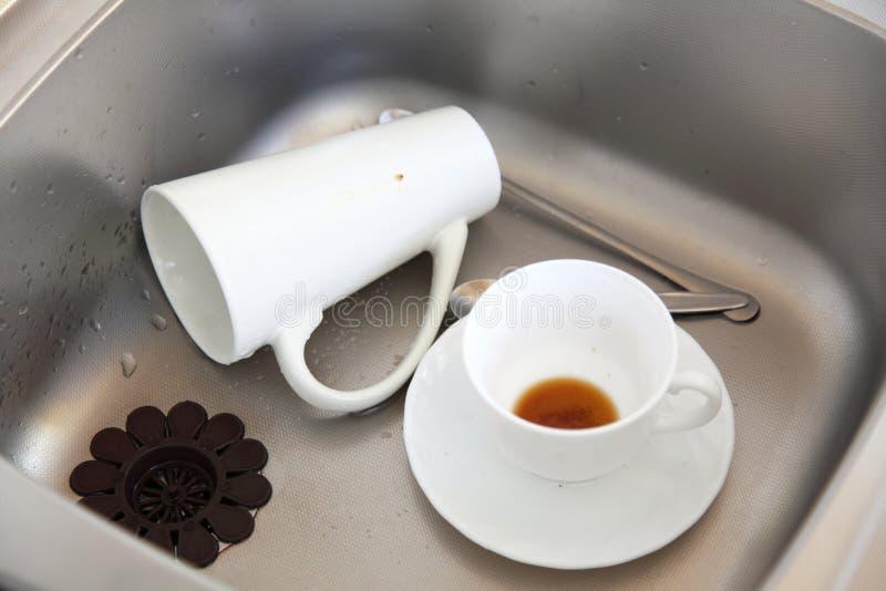 Lavatura dei piatti. Piatti bianchi nel lavandino di cucina. immagine stock libera da diritti