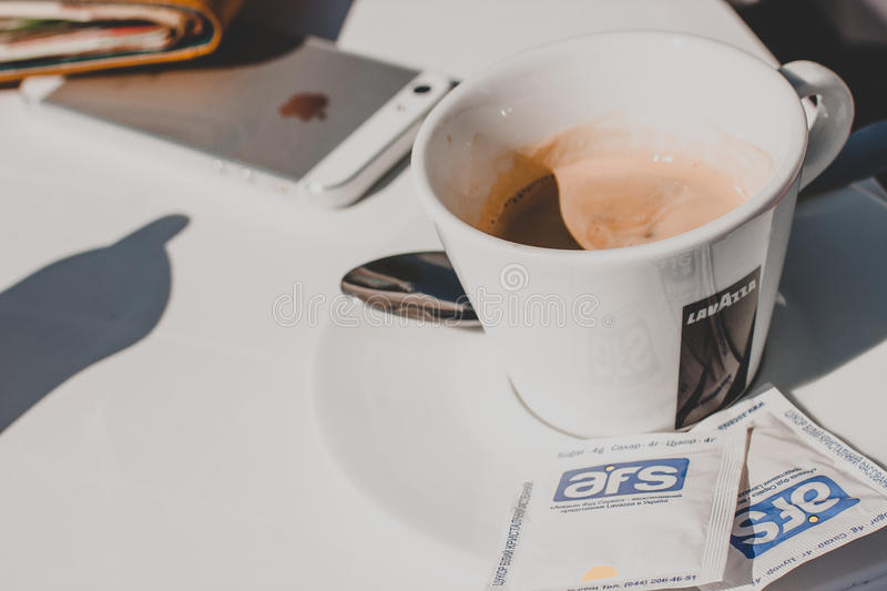 Lavazza kopp av coffe och iPhone arkivfoto