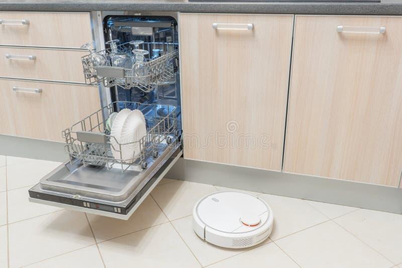 Lave-vaisselle ouvert et aspirateur de robot dans la cuisine Technologie électronique futée moderne de ménage images stock