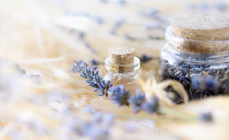 Lavendelätherisches öl und getrocknete Lavendelblumen in der Glasflasche stockfotografie