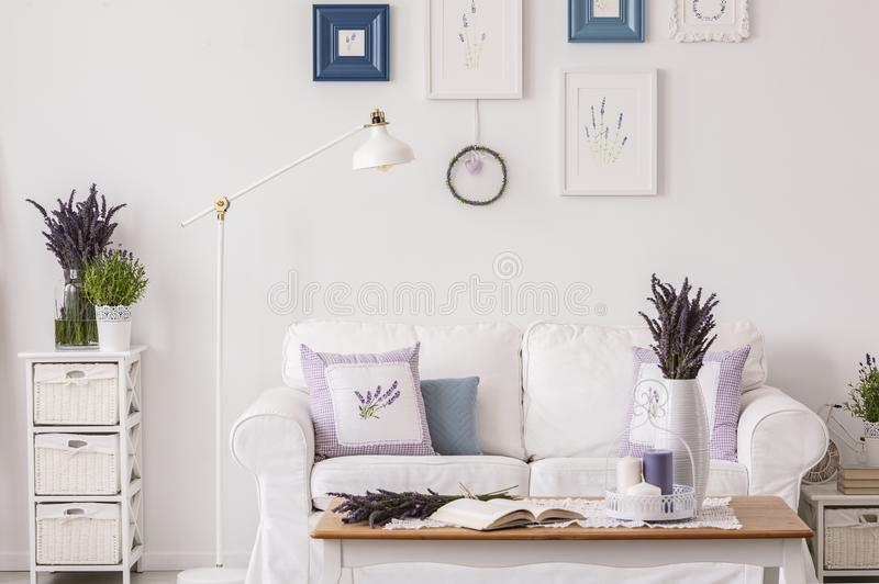 Lavendel blommar på kabinettet bredvid lampan och vitsoffan i vardagsruminre med tabellen och affischer Verkligt foto royaltyfri bild