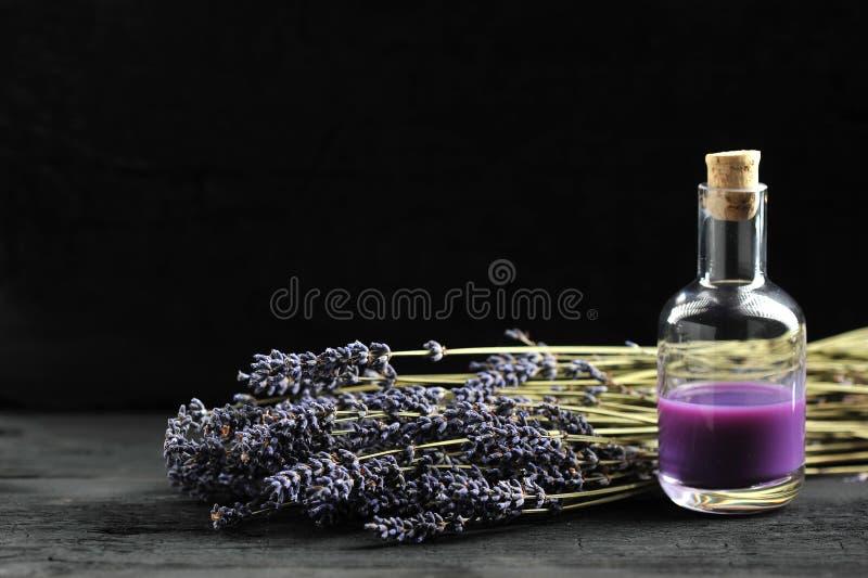 Lavendel, Lavendelöl auf dunklem hölzernem Hintergrund stockbilder