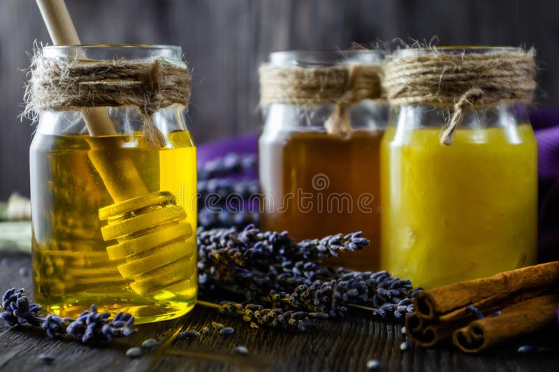 Lavendel och växt- honung i exponeringsglaskrus med honungskeden på mörk träbakgrund arkivfoto