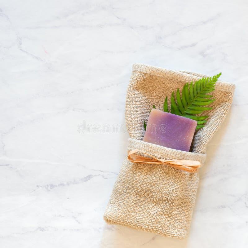 Lavendel roch Seife mit Tan Washcloth und grünem Fern Frond auf Badezimmer-Grau-und weißermarmoroberfläche mit Raum oder Raum für stockfoto
