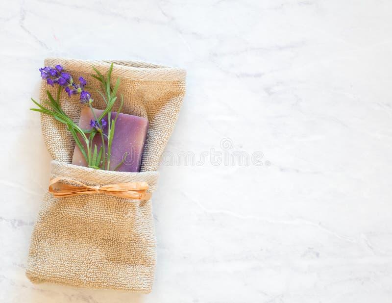 Lavendel roch Seifen-und Blumen-Blüten mit den frischen grünen Blättern, die in Tan Washcloth auf Badezimmer-Grau-und weißermarmo stockfotografie