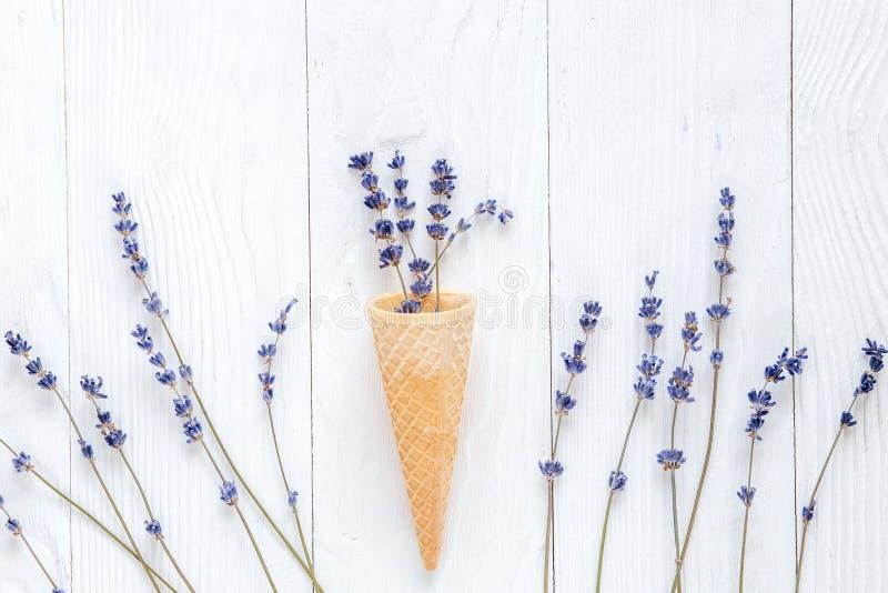 Lavendelbloemen met het model van de wafelkegel op witte bureau hoogste mening als achtergrond royalty-vrije stock foto
