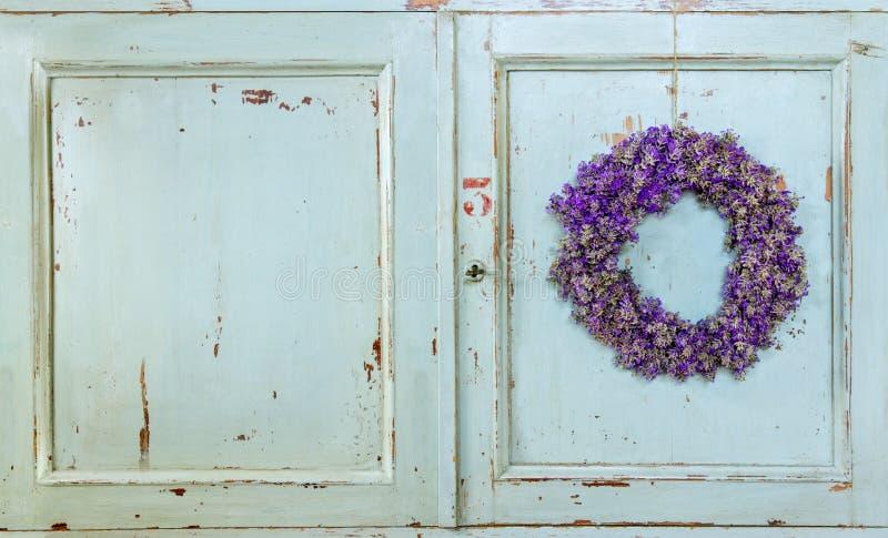 Lavendelblommakrans som hänger på en gammal dörr royaltyfri bild