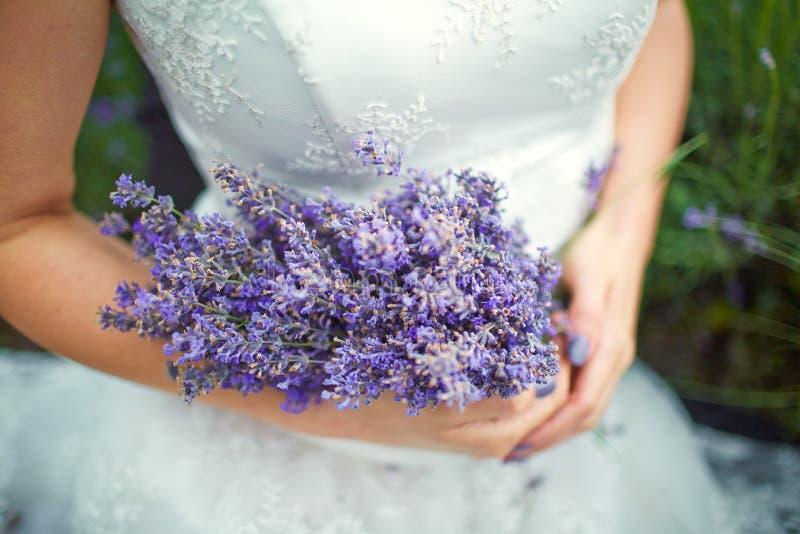 Lavendelbukett i händer av bruden arkivfoton